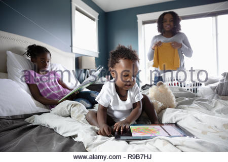 Mother folding laundry while children read and play on bed - Stock Photo