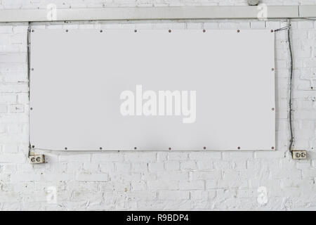 White banner on white brick wall as a good mock up for design - Stock Photo