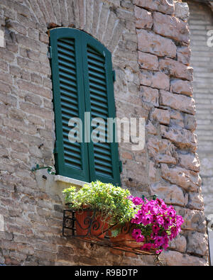 Open door into a home in Assisi, Italy with flowers on the stairs - Stock Photo
