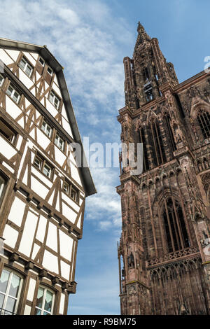 Contrast between Strasbourg Cathedral and old medieval house in Strasbourg, France - Stock Photo