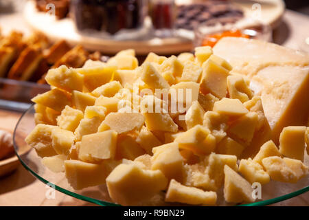 Closeup of plate with pieces of Italian parmesan at banquet on the table among various dishes. Concept birthday, buffet, cognac or whiskey presentatio - Stock Photo