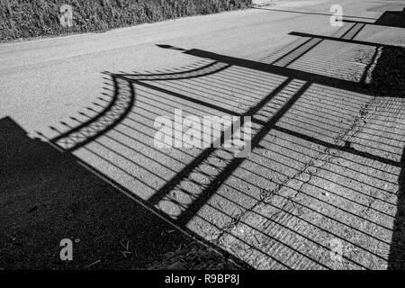 Shadow of beautiful wrought iron garden fence on dusty public road in spring afternoon in Corfu, Greece. Black and white travel image - Stock Photo