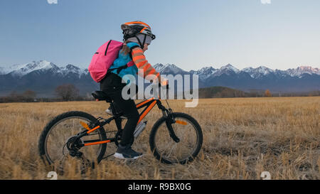 One caucasian children rides bike in wheat field. Little girl riding black orange cycle on background of beautiful snowy mountains. Biker motion ride with backpack, helmet. Mountain bike hardtail. - Stock Photo