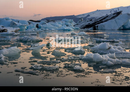 Floating icebergs during sunset at Jokulsarlon glacier in south Iceland near Vik during summer time. - Stock Photo