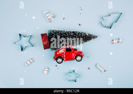 KYIV, UKRAINE - December 12, 2017: Toy red car with fir tree on the roof. Blue pastel background. Flat lay style. Concept of celebrating new year. Christmas mood. - Stock Photo