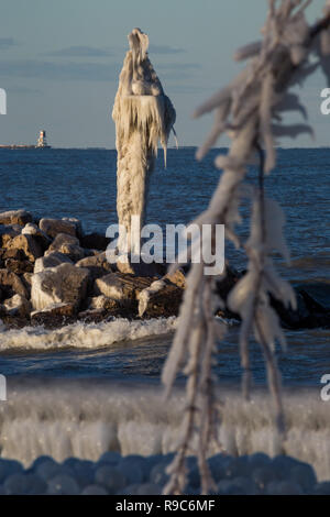 Ice coating a harbor beacon after a winter storm on Lake Michigan in Whiting, Indiana. - Stock Photo