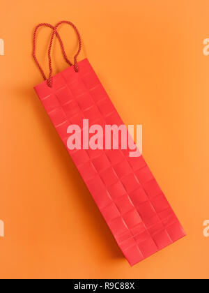 Red cardboard gift bag on orange. Sparse abstract composition. - Stock Photo