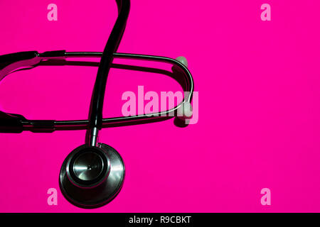 stethoscope with healthcare concept on pink background - Stock Photo
