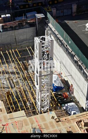Workmen assemble a crane to be used in the construction of a new 42-story high-rise apartment building in midtown Manhattan, New York City. - Stock Photo