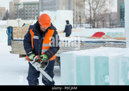 Construction worker in a protective helmet and reflective vest with a chainsaw near the ice plates - Stock Photo