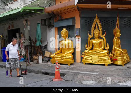 A man passes a factory for Buddha statues in Bamrung Muang Road, Bangkok, Thailand, a centre for the sale of religious objects - Stock Photo