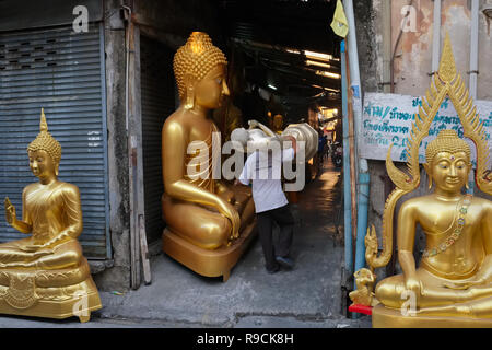 In a factory for Buddha statues in Bamrung Muang Road, Bangkok, Thailand, an employee carries a half-finished statue, passing other Buddha statues - Stock Photo