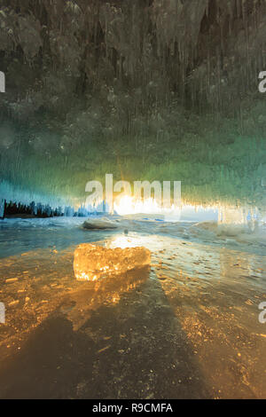 sunset in a cave grotto with icicles in the winter on Olkhon Island, Lake Baikal