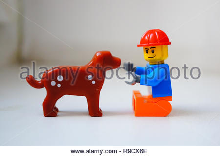 Poznan, Poland - December 22, 2018: Lego toy man having fun with his best dog friend in soft focus background.  - Stock Photo