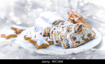 Christmas Stollen sliced on a plate with cinnamon stars - Stock Photo