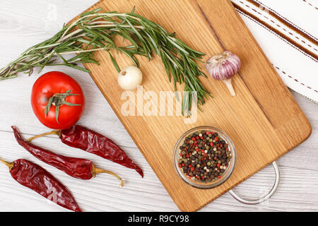 Ingredients for cooking meat or fish. Garlic, allspice peppers in glass bowl, chili pepper, tomato, onion and rosemary on a wooden cutting board. Top  - Stock Photo