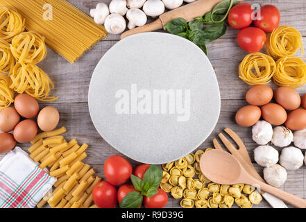 pasta, vegetables, eggs, with dish in the middle on wooden background - Stock Photo