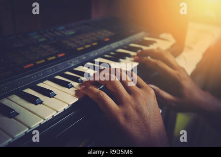 synthesizer piano player musician playing keyboar / MIDI keyboard electronic hands playing different chords on old piano keys on dark background vinta - Stock Photo