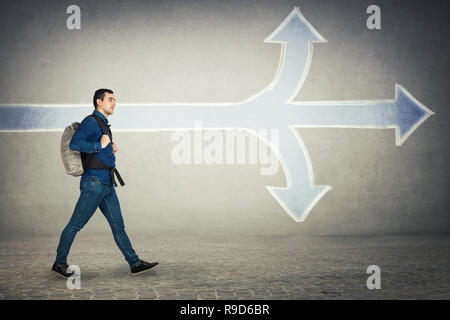 Young man traveler walking carry a backpack choose the direction to go as arrows splitted in three different ways. Up, down and ahead choice. Difficul - Stock Photo