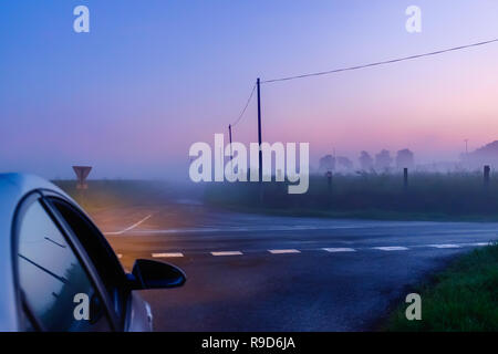 Car stopped at a crossroad in the Orne countryside on a foggy evening at the blue hour, Normandy France - Stock Photo