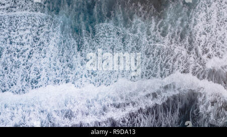 Overhead shots of waves crashing onto a black sand beach on the big island of Hawaii - Stock Photo