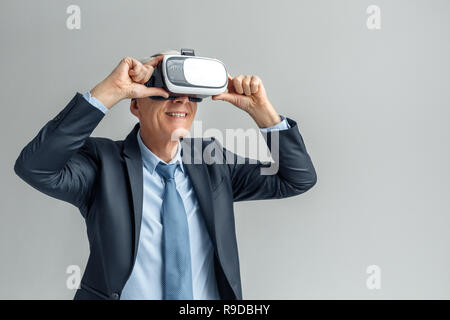 Senior business man wearing virtual reality headset studio standing isolated on gray wall watching video smiling happy - Stock Photo
