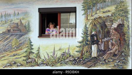 05.07.2004, Wolkenstein, Saxony, Germany - Eine junge Frau schaut aus dem Fenster eines mit erzgebirgischen Motiven bemalten Hauses in Wolkenstein im  - Stock Photo
