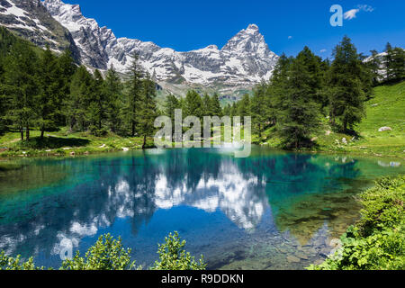 Summer alpine landscape with the Matterhorn (Cervino) reflected on the Blue Lake (Lago Blu) near Breuil-Cervinia, Aosta Valley, northern Italy - Stock Photo