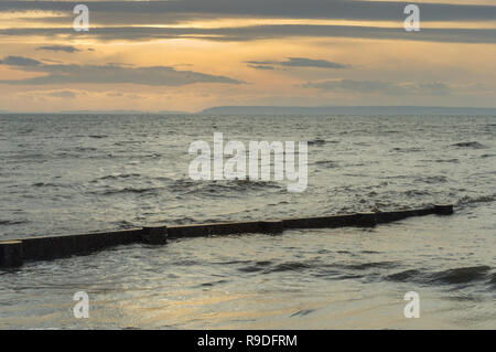 Wooden beach groin being gradually submerged by incoming ocean tide at sunset. Crescent Beach, British Columbia, Canada. - Stock Photo