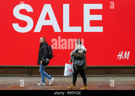 Oxford Street. London, UK. 23rd Dec, 2018. Shoppers walk in front of a large SLAE window display at H&M store. Last minute Christmas shoppers take advantage of pre-Christmas bargains in Oxford Street in London. Fewer shoppers have been reported shopping in Britain's high streets as online sales increase. Credit: Dinendra Haria/Alamy Live News