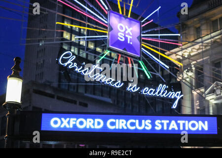 London, UK. 23rd Dec 2018. Christmas decorations and wet surface warnings at Oxford Circus. Shoppers with last minute purchases rush through the sales in the West End of London on the Sunday before Christmas, taking in the colourful decorations and captivating light displays in the capital. Credit: Imageplotter News and Sports/Alamy Live News - Stock Photo