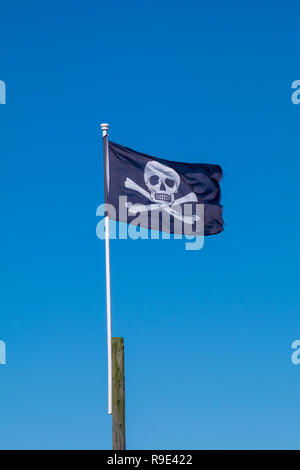 A jolly roger pirate flag (the skill and cross bones) flies in the wind against a blue sky - Stock Photo
