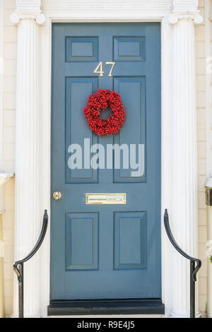 An understated traditional red popcorn berry Christmas wreath decorates the wooden door on a historic home for the holidays on Tradd Street in Charleston, South Carolina. - Stock Photo