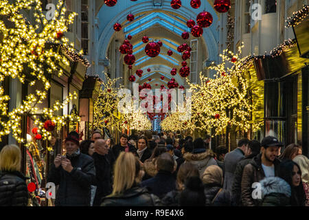 A packed Burlington Arcade in Mayfair, London at Christmas time as shoppers do last minute shopping - Stock Photo