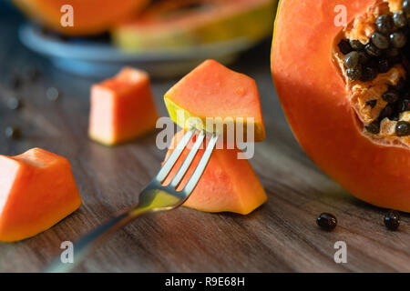 Papaya, papaya on a plate and slices of papaya  on a fork, close up - Stock Photo