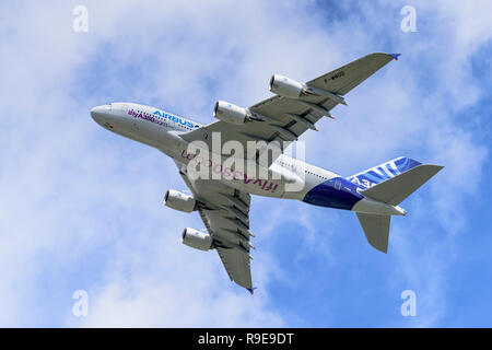 Airbus A380 passenger airliner shows its underside and flight control surfaces during a clean pass from right to left. - Stock Photo