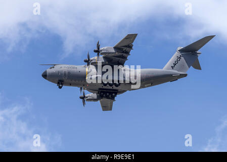 Airbus A400M Atlas military transport aircraft performs a dirty pass (wheels down), flying overhead from right to left. - Stock Photo