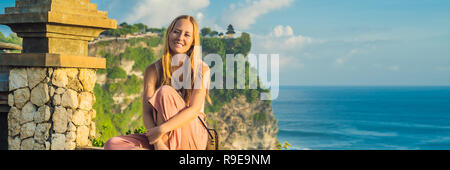 Young woman traveler in Pura Luhur Uluwatu temple, Bali, Indonesia. Amazing landscape - cliff with blue sky and sea BANNER, LONG FORMAT - Stock Photo