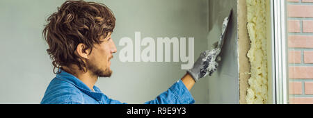 master is applying white putty on a wall and smearing by putty knife in a room of renovating house in daytime BANNER, LONG FORMAT - Stock Photo