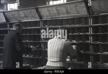 1948, two Royal Mail staff workng inside a postal sorting office, England, UK. Picture shows them putting letters into small cubicles for the different streets.