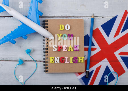 Concept of learning English language - colorful letters with text 'Do you speak English', flag of the UK, airplane, headphones on white wooden backgro - Stock Photo