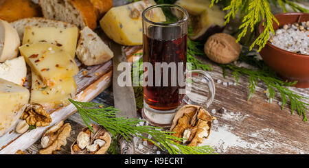 Assortment of cheeses, red wine, nuts and spices on a wooden table. Food banner - Stock Photo