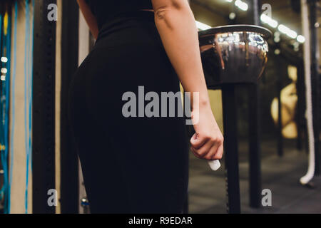 Cropped shot of young female athlete clapping hands with chalk powder before strength training. - Stock Photo