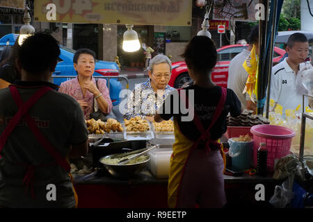 A roadside food stall in Yaowarat Road, Chinatown, Bangkok, Thailand, on a late afternoon; seen from the vantage point of the vendors - Stock Photo
