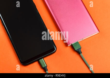 the smartphone is charging from a pink power bank on a yellow background - Stock Photo