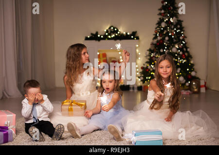 Kids open Christmas presents new year holiday lights sparklers - Stock Photo