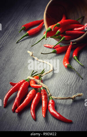 Closeup on red hot chili peppers tied with a string on dark wooden background. Food background. - Stock Photo