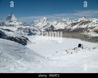 horizontal view of the Monte Rosa mountain hut with the famous Matterhorn peak and surrounding winter landscape in the background - Stock Photo