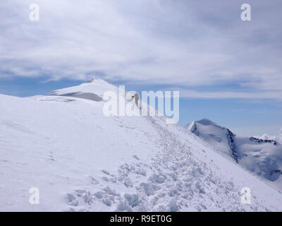 mountain climber hiking along a long snow ridge on his way to a high alpine summit with tracks in the foreground - Stock Photo