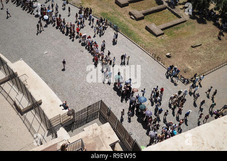 Aerial view from the Colosseum of toursists queuing on a hot day in Rome, Italy, holding parasols and umbrellas - Stock Photo